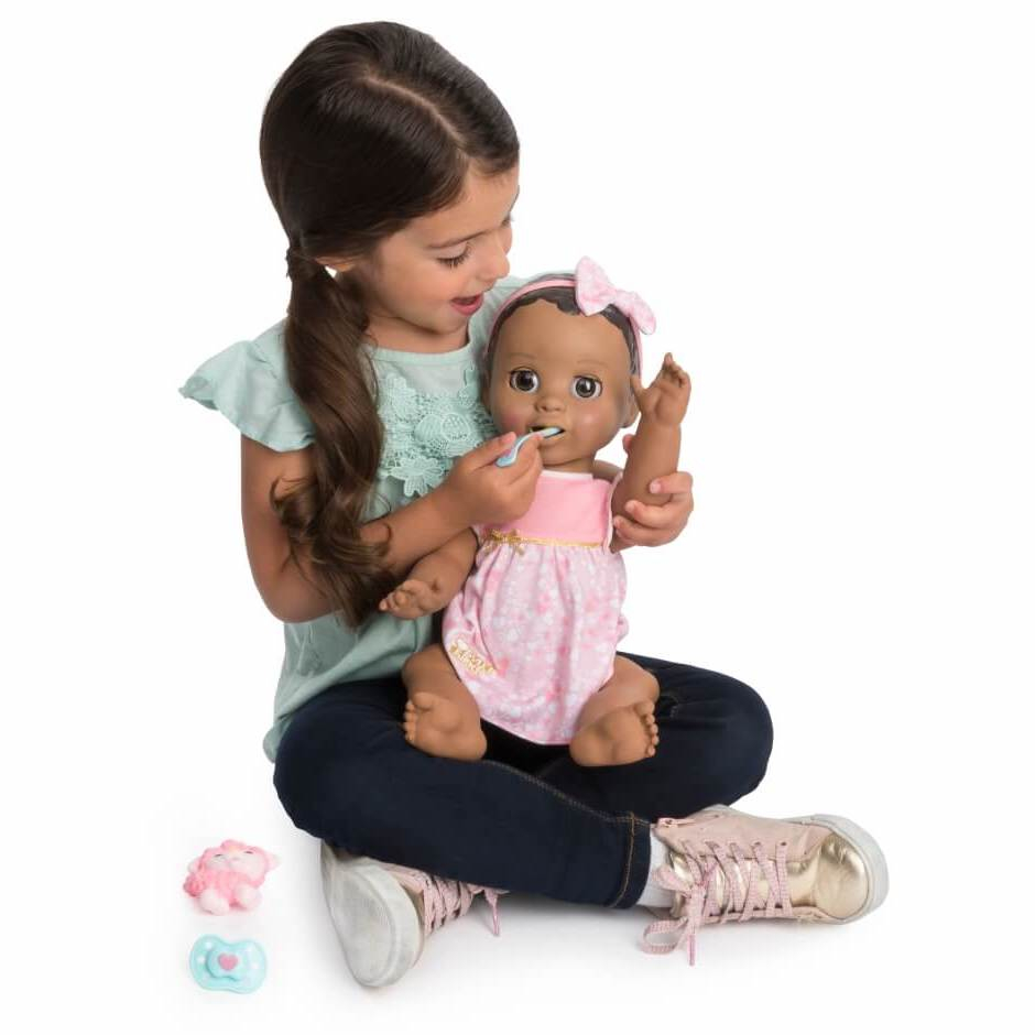 kid feeding a doll